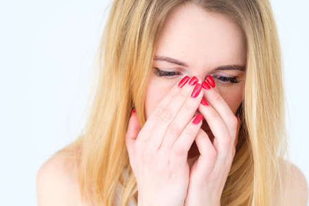 emotion face. bad news grief trouble. woman covering her face with hands. young beautiful blond girl portrait on white background.