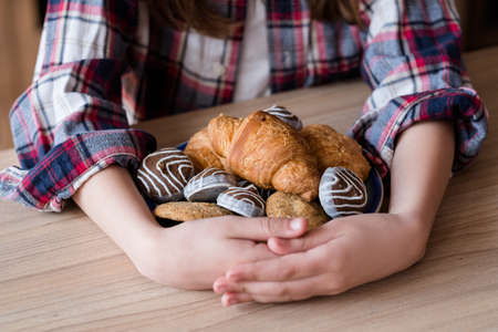 child sugar addiction. unhealthy eating habits. confectionery and puff pastry overeating. girl hugging a plate of croissants and chocolate sweets.
