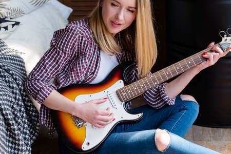 musical talent and hobby. woman playing guitar and singing sitting at home. artistic leisure Imagens