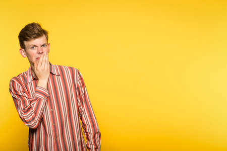 squeamishness aversion nausea repulsion. man is disgusted. portrait of a guy on yellow background. copyspace for advertisement. Stock Photo