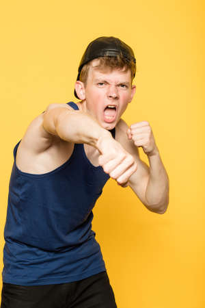 cocky arrogant fighter. street thug and hooligan. man punching a fist. portrait of a young guy on yellow background. emotion facial expression. feelings and people reaction.