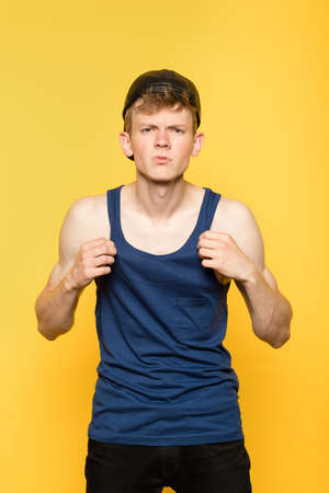 defiance and arrogance. cocky and provocative man. disrespectful thug in a tank top. portrait of a young guy on yellow background. emotion facial expression. feelings and people reaction. Stock Photo - 104260367