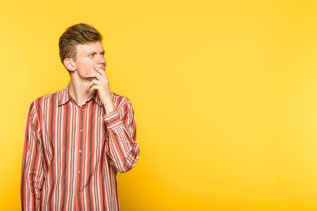 pensive thoughtful contemplative brooding man looking sideways. portrait of a young guy on yellow background. copyspace for advertisement. Фото со стока