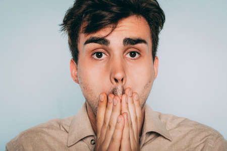 regret and remorse. sad distraught man covering mouth with hand. portrait of a young brunet guy on light background. emotion facial expression. feelings and people reaction concept.