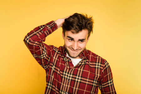 cute troublemaker smiling mischievously. relaxed confident delighted man contemplating prank. portrait of a handsome brunet guy on yellow background. emotion facial expression. Stock Photo