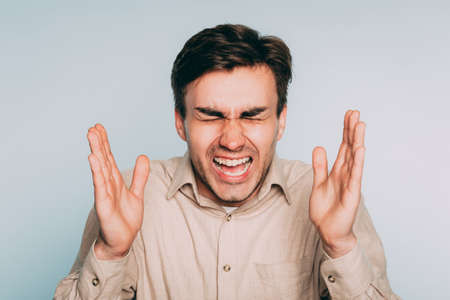 overwhelming pain agony suffering. emotional stress. man screaming. portrait of a young brunet guy on light background. emotion facial expression. feelings and people reaction concept.