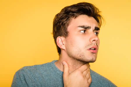 worried alarmed concerned man nervously touching neck looking sideways. portrait of a young handsome brunet guy on yellow background. emotion facial expression. feelings and people reaction concept.