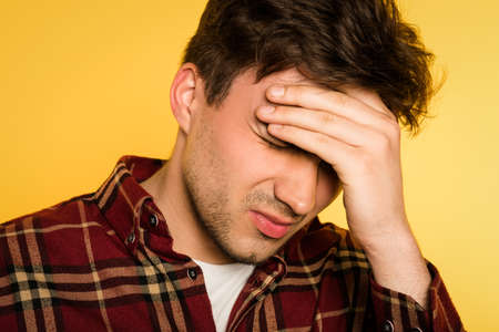 headache or migraine. man in pain clutching his head. discomfort ache and misery. portrait of a young brunet guy on yellow background. emotion facial expression. feelings and people reaction concept.