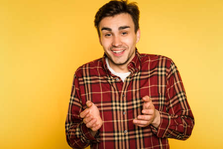 surprised amused speechless man smiling. portrait of a young handsome brunet guy on yellow background. emotion facial expression. feelings and people reaction concept.
