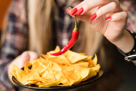 hot spicy chips. pungent fiery food snack. woman hand holding nacho crisps and red chili pepper Stock Photo