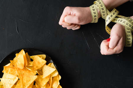 healthy diet eating. weightloss and fit body. woman hands tied with measuring tape. no chips today.