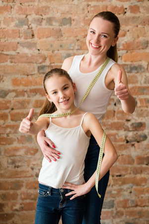 Healthy and fit family. slim and beautiful mom and daughter watch their weight.
