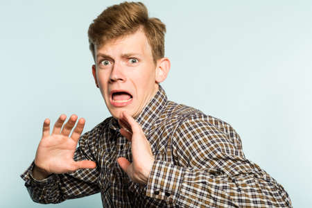 Scared frightened man. cowardly comical reaction. portrait of a young guy on light background. emotion facial expression.