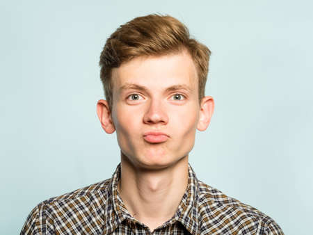 Cute smiling man pouting. joyful playful behavior. portrait of a young guy on light background. emotion facial expression. feelings and people reaction.