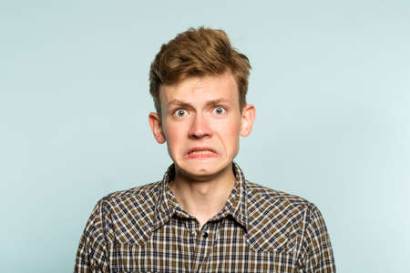 Awkward gawky fumbling oafish dorky man facial expression. portrait of a young guy on light background. emotion facial expression. feelings and people reaction. Zdjęcie Seryjne