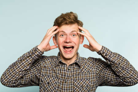 Crazy happy overexcited mad bonkers wild man with a wide grin. portrait of a young guy on light background. emotion facial expression. feelings and people reaction.