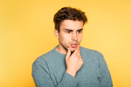 Puzzled bewildered man thinking over something or contemplating. scratching his beard. portrait of a young brunet guy on yellow background. emotion facial expression. feelings and people reaction concept.