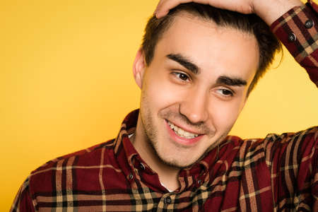 Smiling happy relaxed man smoothing his hair looking sideways. portrait of a young handsome brunet guy on yellow background. emotion facial expression. feelings and people reaction concept.