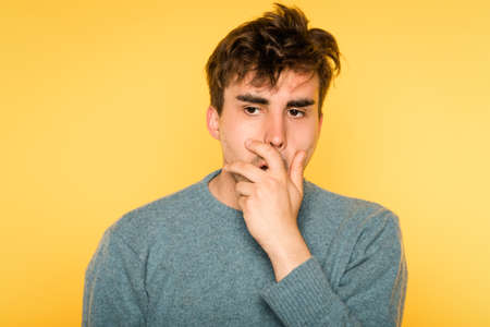 Regret and remorse. sad distraught man covering mouth with hand. portrait of a young handsome brunet guy on yellow background. emotion facial expression. feelings and people reaction concept.