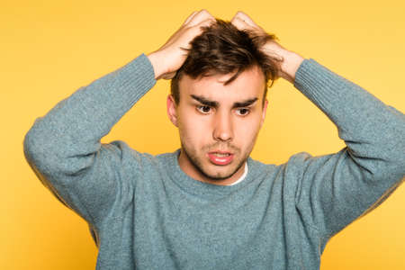Sad worried distraught disappointed man pulling hair out. portrait of a young handsome brunet guy on yellow background. emotion facial expression. feelings and people reaction concept. Stock Photo
