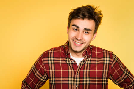Ruffled disheveled laid back man smiling. portrait of a young handsome brunet guy on yellow background. emotion facial expression. feelings and people reaction concept.