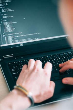 Programmer writing code on his laptop. web developer designing application. internet technologies concept Foto de archivo