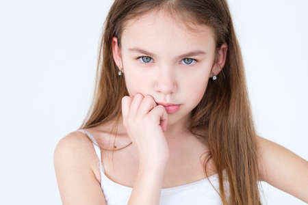 Serious child thinking over something. hand under the chin. little girl portrait on white background. mood feelings personality and facial expression concept