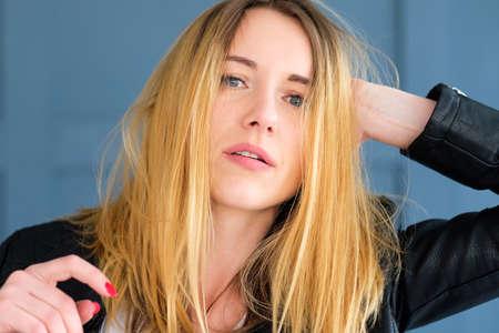 Jeune femme ébouriffée en blouson de cuir noir avec des cheveux ébouriffés. portrait de jeune fille blonde sur fond bleu