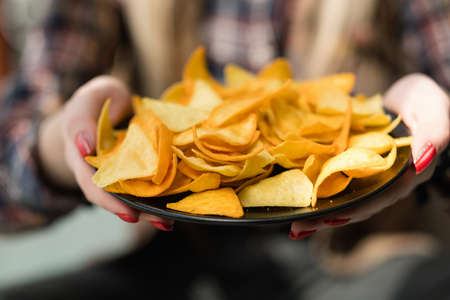Homemade fried tortilla nacho chips. woman hand offering a plate of natural fried crisps. delicious salty food snack