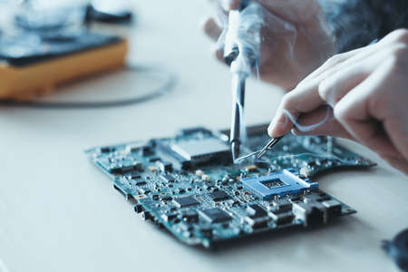 technology microelectronics science education. engineer student learning to solder an electronic component on computer motherboard