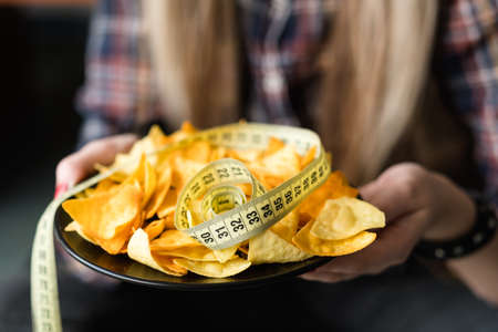 unhealthy fast food snacks. weight gain due to bad nutrition habits. woman hands holding chips with a measure tape on a plate 版權商用圖片