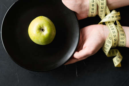 losing weight fitness and slim figure. power of will and restriction in the female fight for perfection. woman hands tied with measuring tape holding a plate with one apple