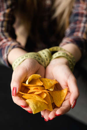self control will power and restraint. dieting weightloss and fitness. woman hands tied with measuring tape holding a pile of chips. food temptation Stock Photo