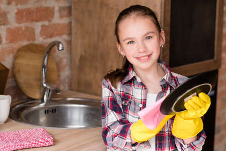 kitchen clean up and washing dishes. young kid girl wiping a plate. child upbringing and household duties.