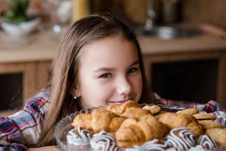 child sugar addiction. unhealthy eating habits. confectionery and puff pastry overeating. little girl smiling at the sight of croissants and chocolate sweets plate