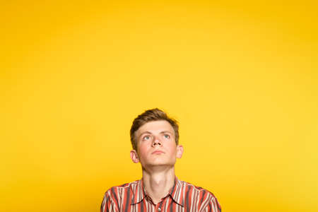 serious concentrated handsome man looking up. portrait of a young guy on yellow background popping up or peeking out from the bottom. copyspace for advertisement. 写真素材