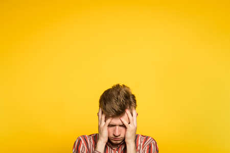 devastated stricken man in despair. failure and loss concept. portrait of a young guy on yellow background popping up or peeking out from the bottom. copyspace for advertising.