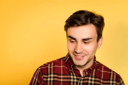 smiling mysterious man looking sideways. portrait of a young handsome brunet guy on yellow background. emotion feelings and people reaction concept. Stock Photo