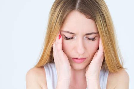 Gefühlsgesicht. Erschöpfung durch Kopfschmerzen. müde Frau massiert ihre Schläfen. junges schönes blondes Mädchenporträt auf weißem Hintergrund.