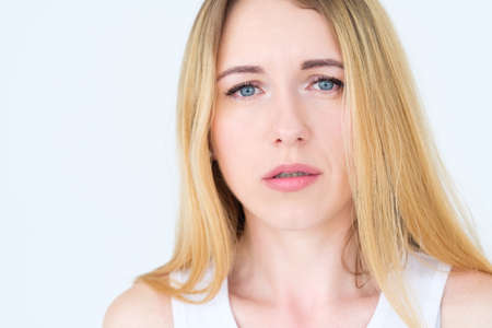 emotion face. moody grumpy sullen upset woman. young beautiful blond girl portrait on white background. Banco de Imagens