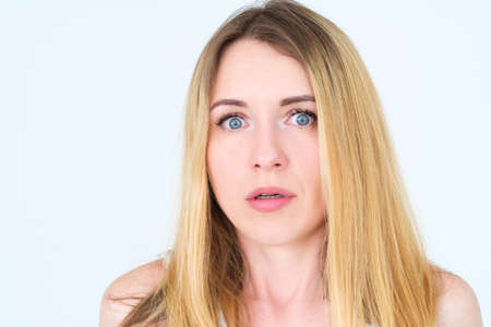 emotion face. overwhelmed perplexed shocked surprised astounded woman young beautiful blond girl portrait on white background. Stock Photo