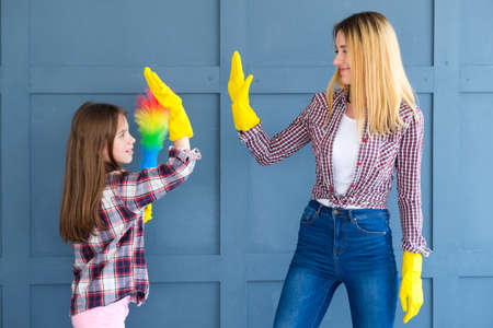 family teamwork. home cleaning and household chores. mom and kid daughter giving high five.