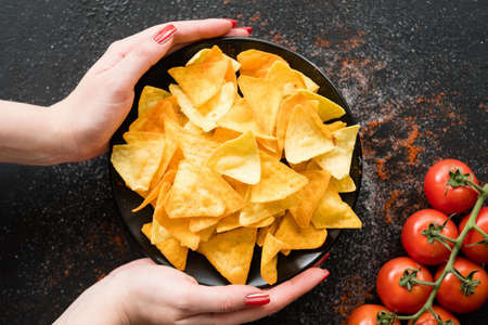 homemade fried tortilla nacho chips. spicy crisps on a plate on dark background. delicious salty food snack