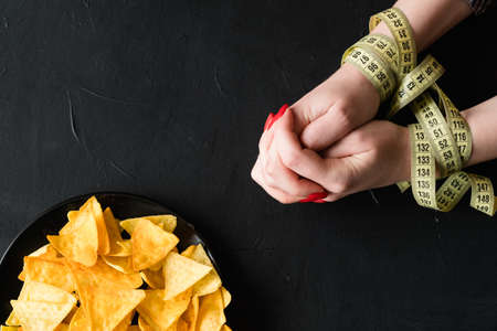 diet restrictions vs fast food. no chips snack. healthy lifestyle choices. woman hands tied with measuring tape. Stock Photo