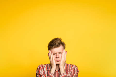 sad rueful depressed cheerless man covering his face in hands. portrait of a young guy on yellow background popping up or peeking out from the bottom. copyspace for advertisement.
