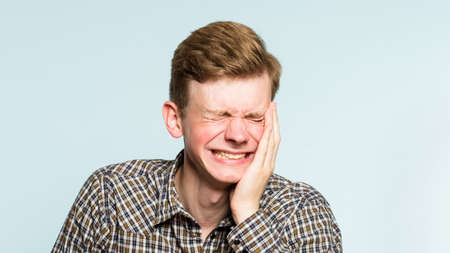 lol lmfao. man laughing hard. joy happiness humor and wide cheerful smile concept. portrait of a young guy on light background. emotion facial expression and feelings. 写真素材