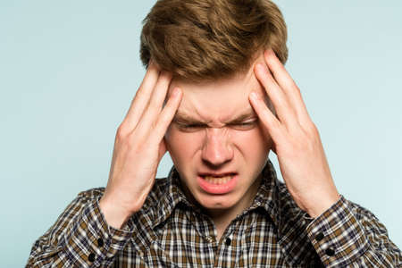 headache or migraine. man in pain clutching his head. discomfort ache and misery. portrait of a young guy on light background. emotion facial expression. feelings and people reaction concept.