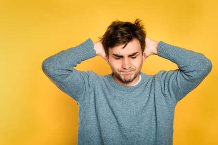 annoyed discontent frustrated disgruntled man. portrait of a young handsome brunet guy on yellow background. emotion facial expression. feelings and people reaction concept. Banco de Imagens - 105078787
