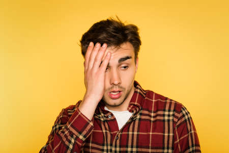 dumbfounded and shocked man clutching his head. feelings of regret remorse and dismay. portrait of a young guy on yellow background. emotion facial expression concept. Imagens