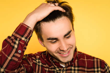 smiling happy relaxed man smoothing his hair looking sideways. portrait of a young handsome brunet guy on yellow background. emotion facial expression. feelings and people reaction concept. Stock Photo